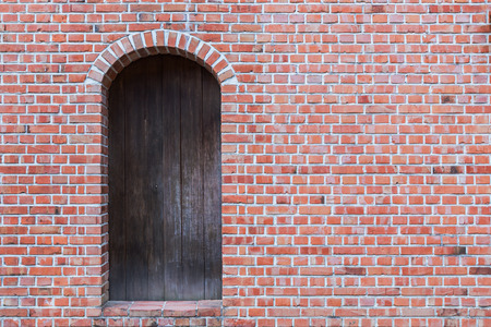 brick: Old red brick wall with wooden door. Stock Photo