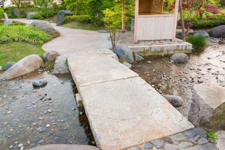 stone path in a japanese garden stone bridge across a tranquil pond stock - Japanese Garden Stone Bridge