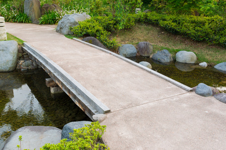 stone path in a japanese garden stone bridge across a tranquil pond photo - Japanese Garden Stone Bridge