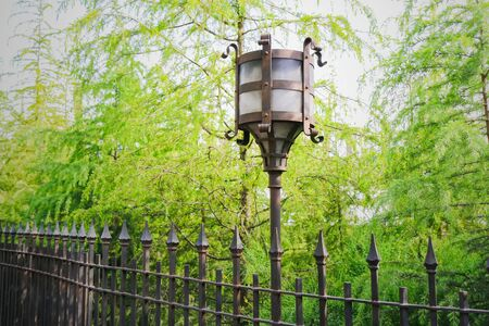 glass fence: Vintage decorative electric street lamp behind iron fence in daytime. single lights in glass enclosures mounted on ornate metal pole.