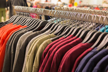 resale: Clothes hanging on a rack in a shopping mall with soft focus. Stock Photo