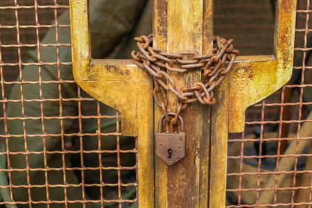 manacle: Retro chain locked metal mesh door with rusty key. Stock Photo
