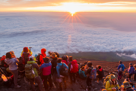 YAMANASHI, JAPAN - JULY 24, 2016 : Crowds of climbers at the summit. Most Japanese climb the Fuji mountain at night in order to be in a position at or near the summit when the sun rises. The morning light is called goraiko, arrival of light.