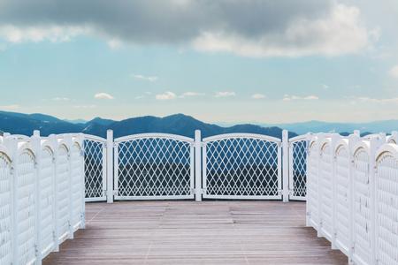 Balcón blanco con piso de madera en perspectiva sobre fondo de naturaleza. Foto de archivo