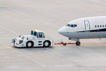 airplane on airport runway with pushback tractor attached to plane nose gear towing by ground vehicle to terminal gate.