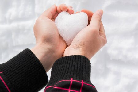 Hands of man with snow heart in winter. Concept love in winter.