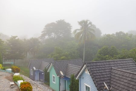 Bungalow resort in nature with morning fog.