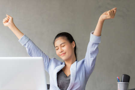 Business women or working lady are stretch oneself or lazily for relaxation on her desk while doing her work in the office.