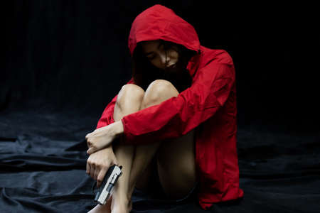 Hopeless Woman in violence with gun in hand sitting in dark room. The concept of stressed woman
