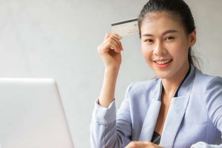 Young asian woman using credit card and laptop for online shopping at home office, smile and happy feeling businesswoman lifestyle concept