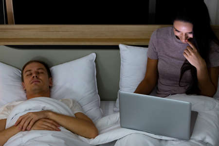 Woman sitting on bed in the night and using laptop computer while husband sleeping beside her.