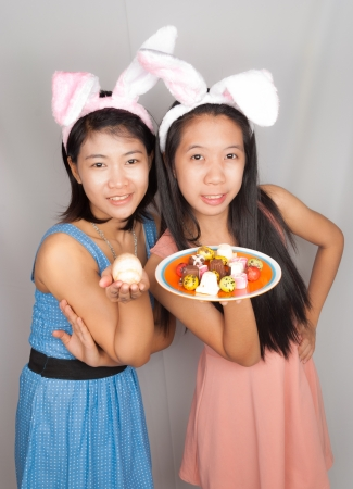 asian bunny: Cute Asian bunny girls hold plate of Easter eggs, chocolate and rock egg. Stock Photo