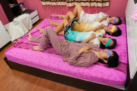Asian Thai girls and boy sleep with turning face up on bed on World Sleeping Day. photo