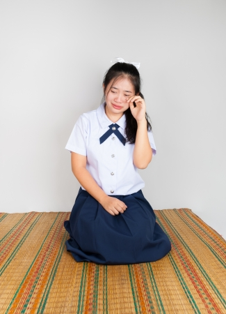 Crying Asian Thai Student in Sitting with Legs Folded Back to One Side photo