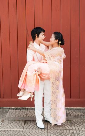 Asian Thai groom is carrying his bride in smiling face. photo