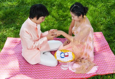 Asian Thai groom is wearing wedding ring to his bride in Thai ceremony with happiness feeling. photo