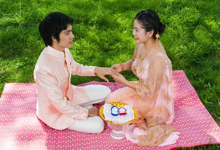 Asian Thai bride is wearing wedding ring to her groom in Thai ceremony with happiness feeling. photo