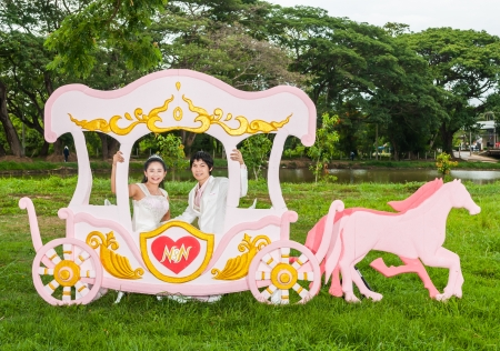 Asian Thai bridal is sitting in romantic carriage with love theme as the Prince and Princess. photo