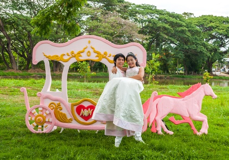Asian Thai groom is carrying his cute bride in front of romantic carriage with love theme as the Prince and Princess. photo