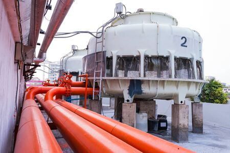 Cooling Tower with Orange Water Pipe on Rooftop  Stock Photo