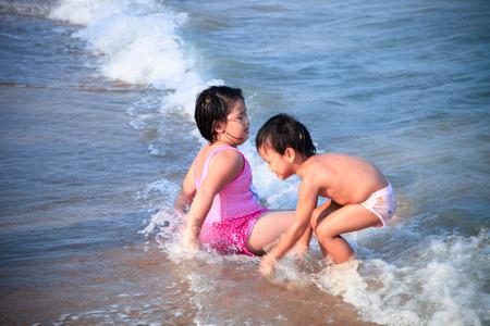 plating: lovely children plating on the beach Stock Photo