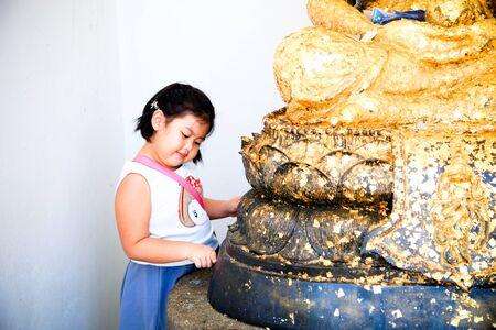 gild: Little Girl doing gild on buddhism statue Stock Photo
