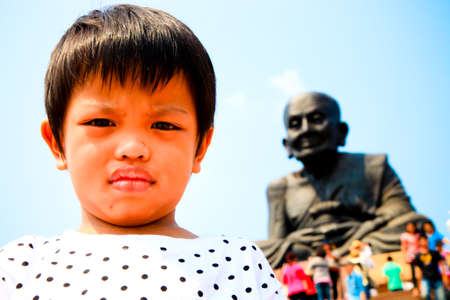 closedup: closedup face asian boy ,background on black buddhism statue