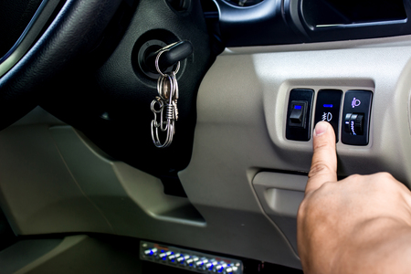 A man repair level headlight switch and push press the button for check and maintenance in the car service concept