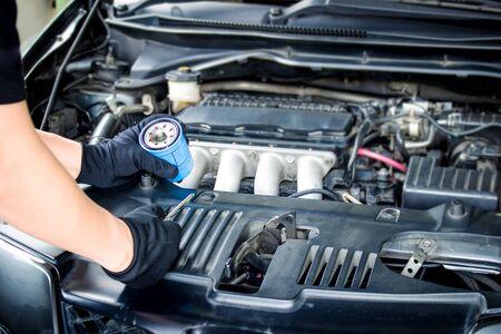 Mechanic man change Engine oil filter for car maintenance concept in engine room