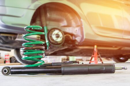 Coil spring and shock absorber on the service shop change and remove old part car maintenance concept