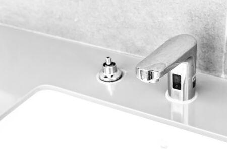 Chiudere il vecchio bagno con rubinetto cromato in acciaio inossidabile e la polvere sulla superficie non si pulisce e il sensore per l'apertura e la chiusura automatica dell'approvvigionamento idrico