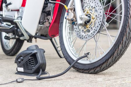 Checking concept air pressure and filling air in the tires with motorcycle with electric pump on road basic maintenance of automobile
