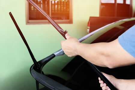 Hand a man unlock and change wiper of glass car in garage shop service and maintenance in rainy season Stock Photo