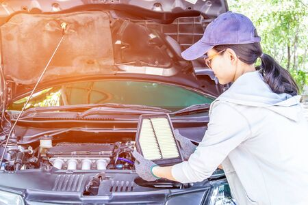 Asia Women change new air filter engine of car basic check and service concept for texture in automobile maintenance work in engine room