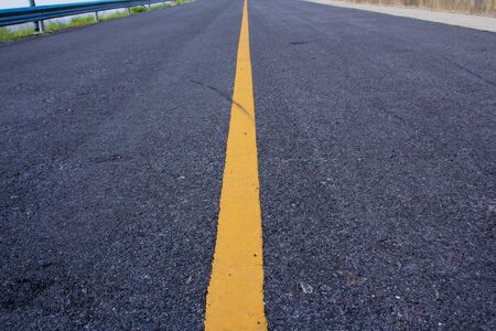 yellow line: new asphalt road with yellow line before sunset
