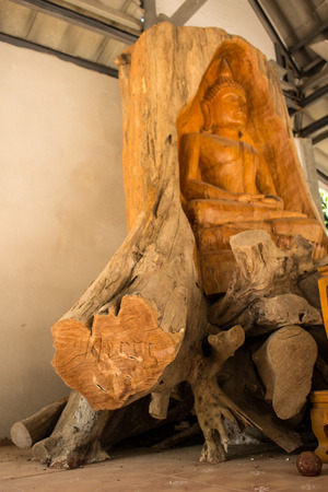 Buddha carved from a tree stump from The teak forests of Lamphun  Public worship, to preserve the forest  This wooden statue is located at Ban Thung Yao Lamphun Thailand  photo