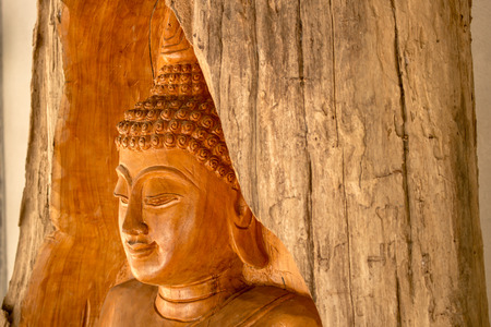 Buddha carved from a tree stump from The teak forests of Lamphun. Public worship, to preserve the forest. This wooden statue is located at Ban Thung Yao Lamphun Thailand. photo