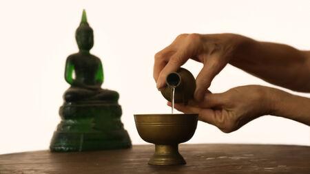 merit: Thai people pour water merit for buddha