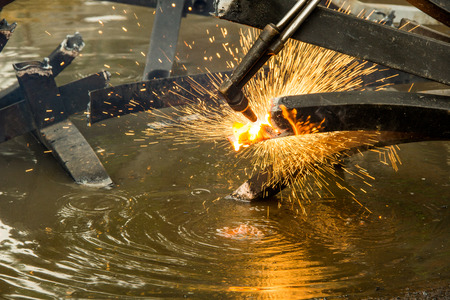 The worker is cutting steel with oxygen gas cutting machine