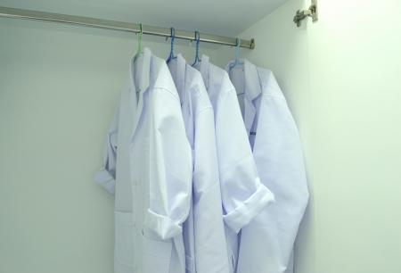 bata de laboratorio: abrigo blanco vestido cuelga en el armario