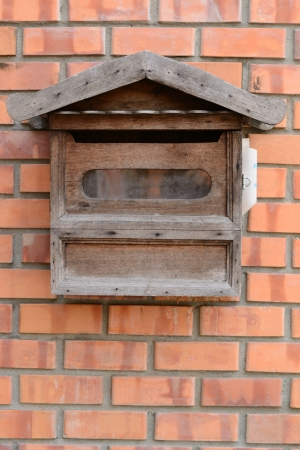 An Old Wooden Mailbox on the Brickwall photo