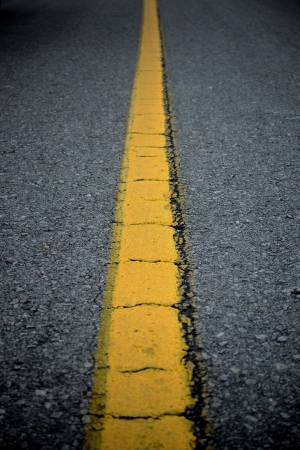 Cracked yellow line on the straight road photo