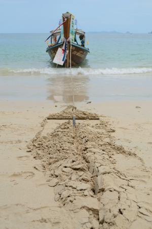 shore line: Boat with the anchor dig in the sand