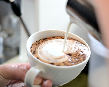 barista poring milk to make a latte art photo