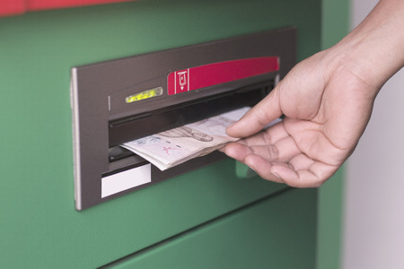 money in hand: Hand taking cash out from green ATM