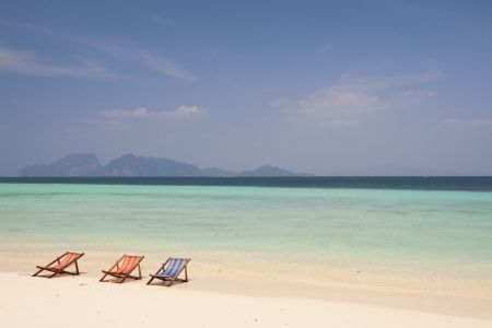 The three beach chairs with the white sand and the blue sky at the Kradan island, Trang, Thailand photo