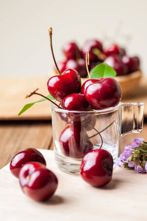 Many fresh cherries in cup on wooden tray photo