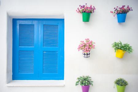 flowerpots: Details of a blue wooden window with flowerpots on the wall