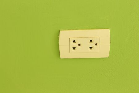 electric outlet: white electric outlet mounted on green wall