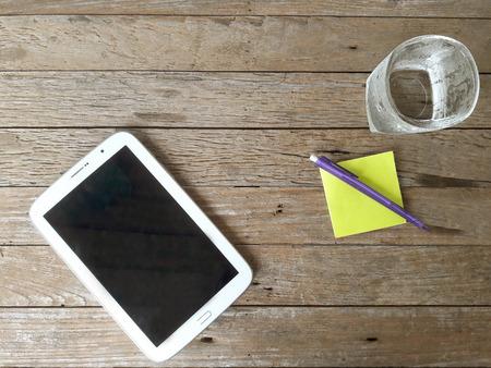 Tablette blanche avec un écran vierge sur la table en bois, bloc-notes, stylo et un verre d'eau placé sur un plancher en bois. Vue de dessus.